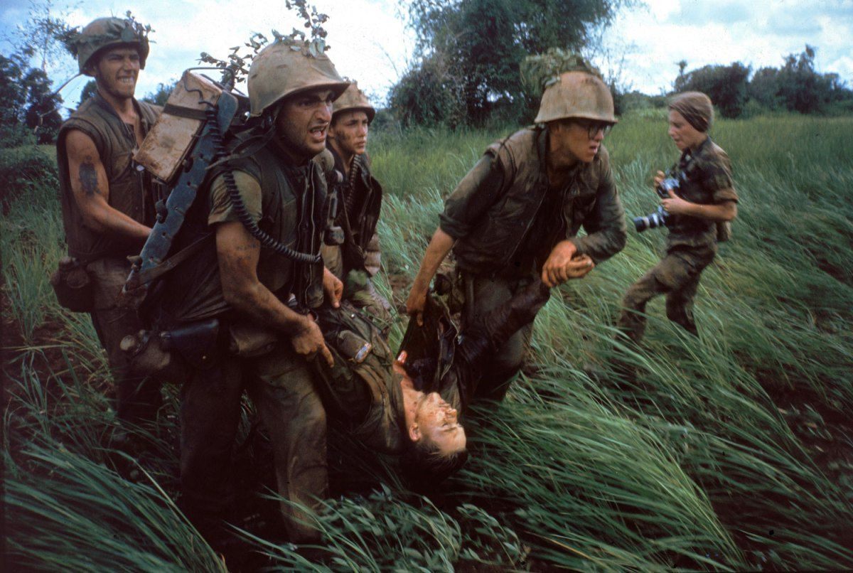 """Four Marines recover the body of a fifth as their company comes under fire near Hill 484."" Vietnam, October 1966. NOTE: At right is the French-born photojournalist Catherine Leroy (1945 – 2006)."