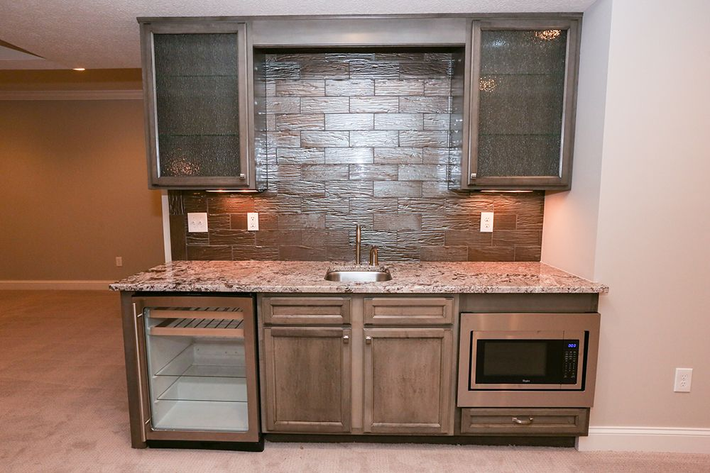 This Wet Bar In The Finished Lower Level Has A Granite Countertop Beautiful Backsplash With A Kitchenaid A Home Additions Kitchen Aid Appliances Custom Homes
