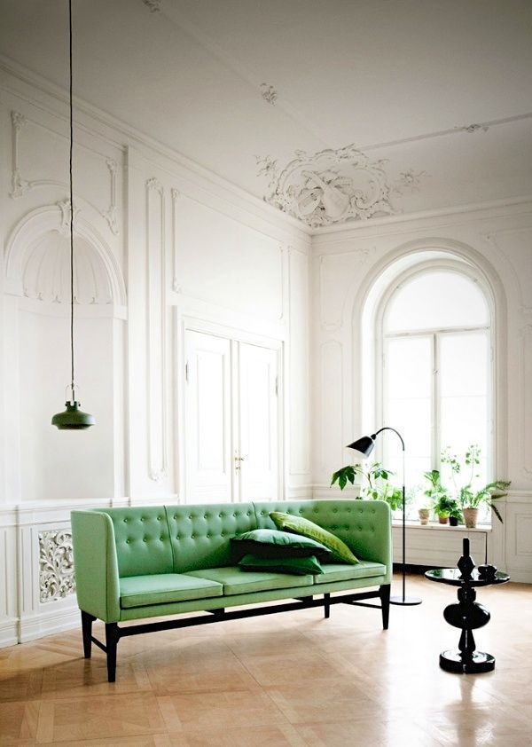 This minimalist white living room is elegant! I love the tall ceilings & intricate wall designs. The green & white color theme creates a chic atmosphere!