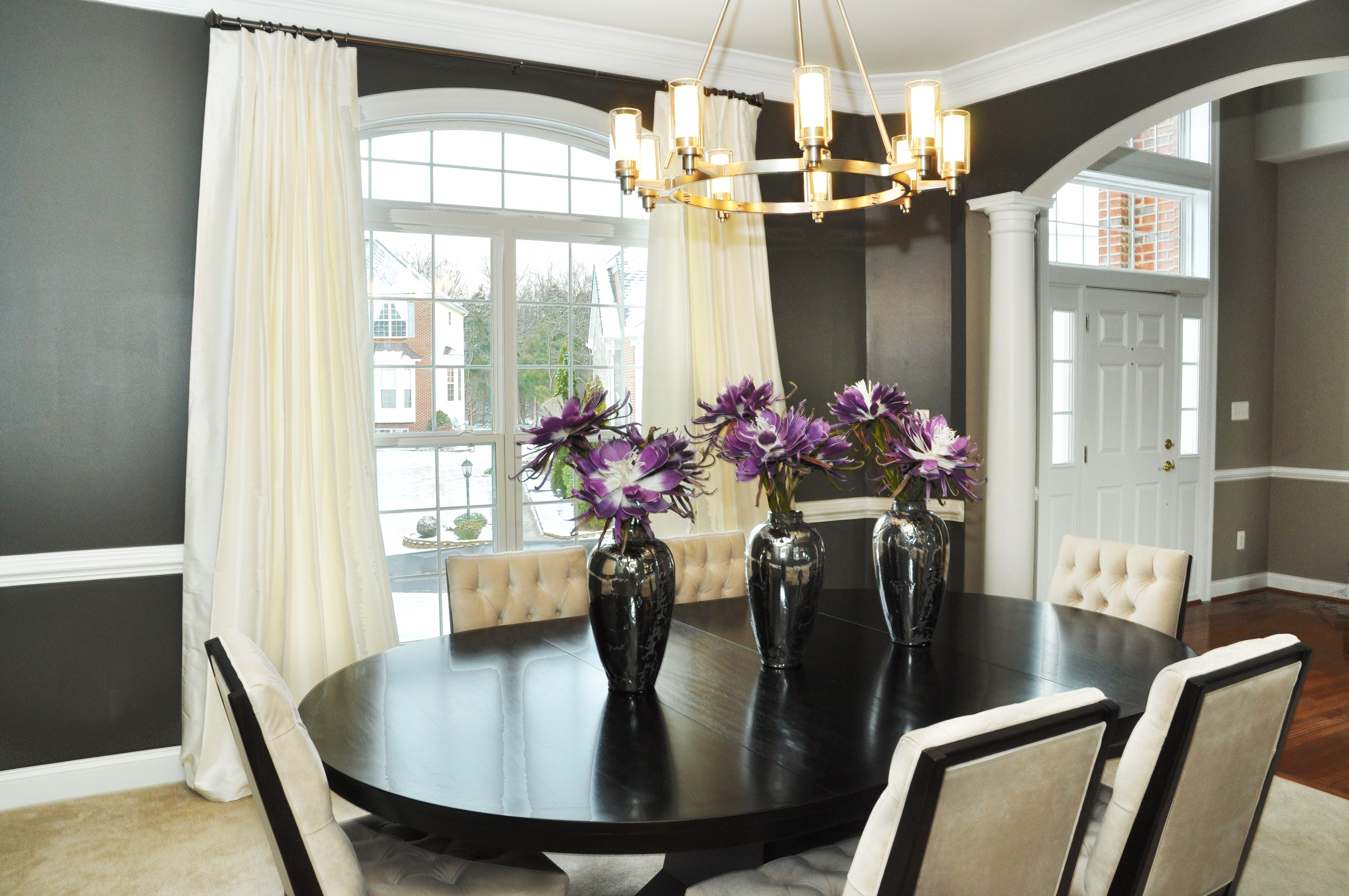 Luxurious white upholstery tufted dining chairs with black oval creative dining room wall decor artistic design ideas elegant black wooden oval dining table feat white tufted dining chairs and white wall curtain windows dzzzfo