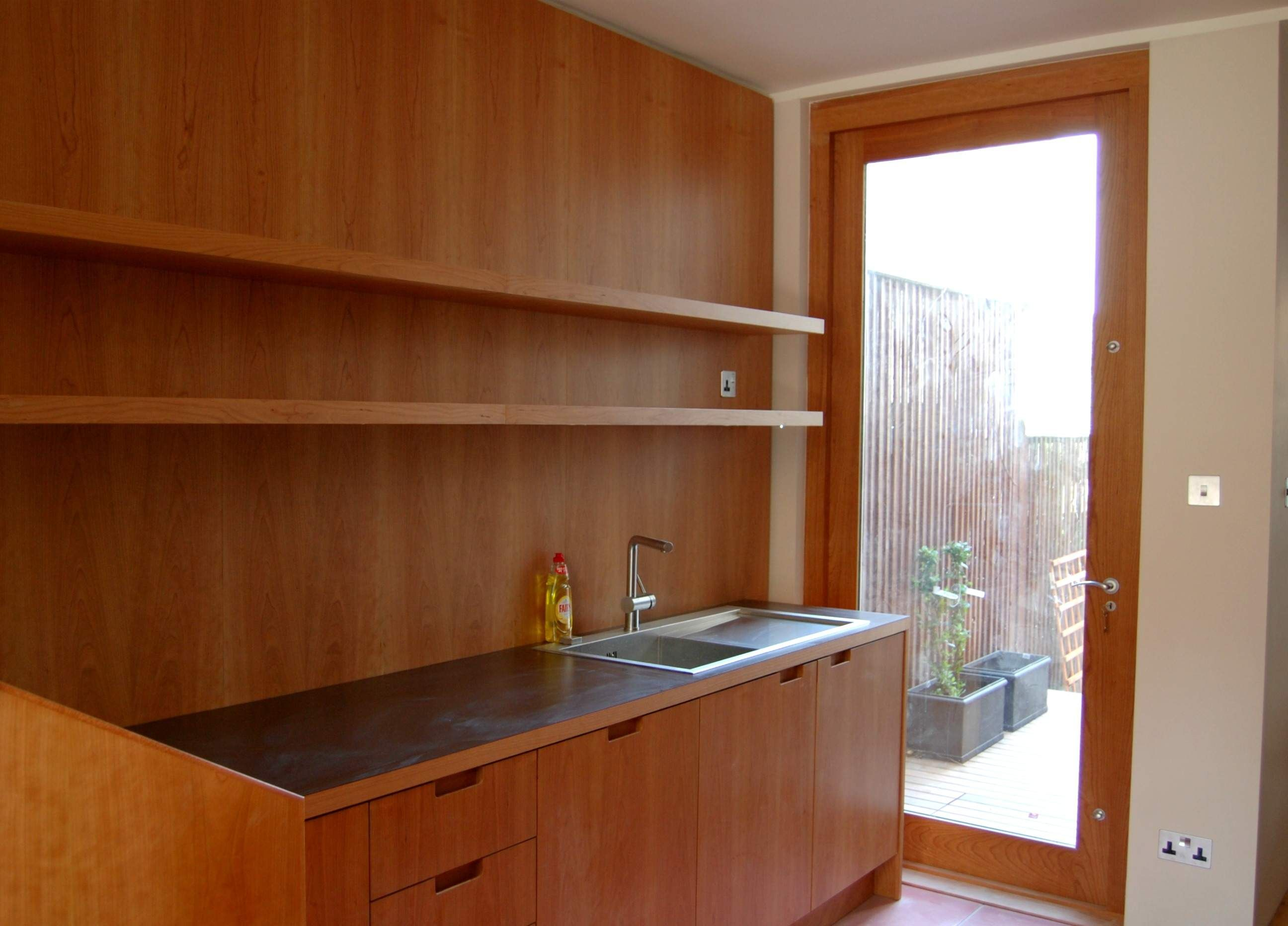 Kitchen With Cherry Wood Wall Panels And Cabinets