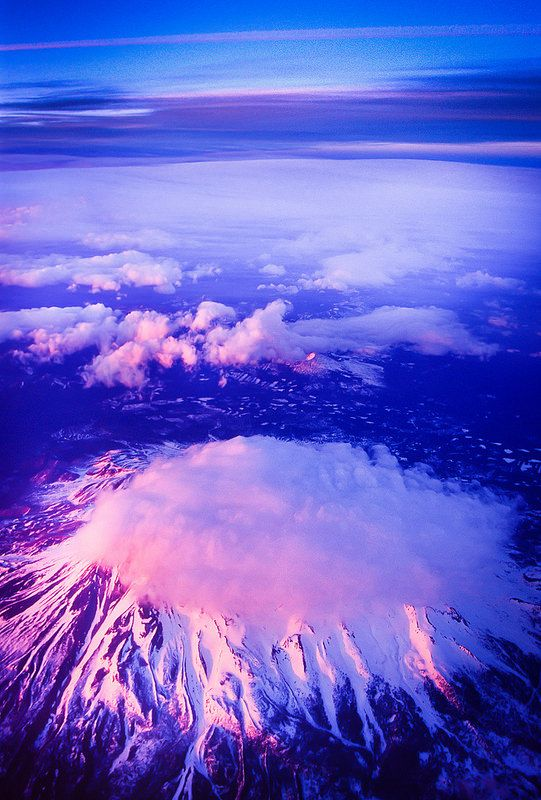 Mt. Shasta under the clouds is a volcano located at the southern end of the Cascade Range in Siskiyou County, California. At 14,179 feet, it is the second highest peak in the Cascades and the fifth highest in California.