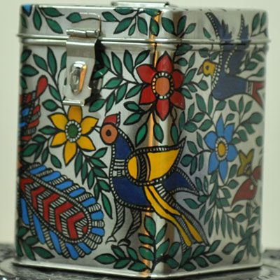 """Madhubani painted Tin Canaster- ideal for storage in the kitchen or other knick knacks.Beautiful, Unique & Durable - Madhubani painted Tin Canaster- ideal for bulk storage in the kitchen or linen or warm clothes .This art form depicts traditional stories painted by women on walls in Mithila, Bihar celebrating weddings, births and festivals. Size - 7""""X5""""X5"""""""