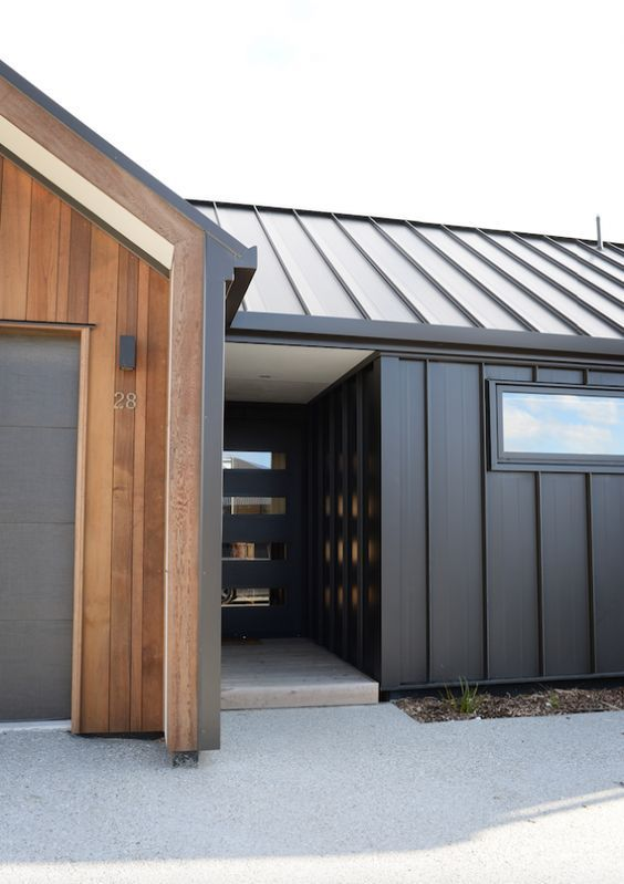 Black Board And Batten Metal Siding And Roofing Garage Facade Is Vertical Teak Siding House Cladding Facade House Exterior House Colors
