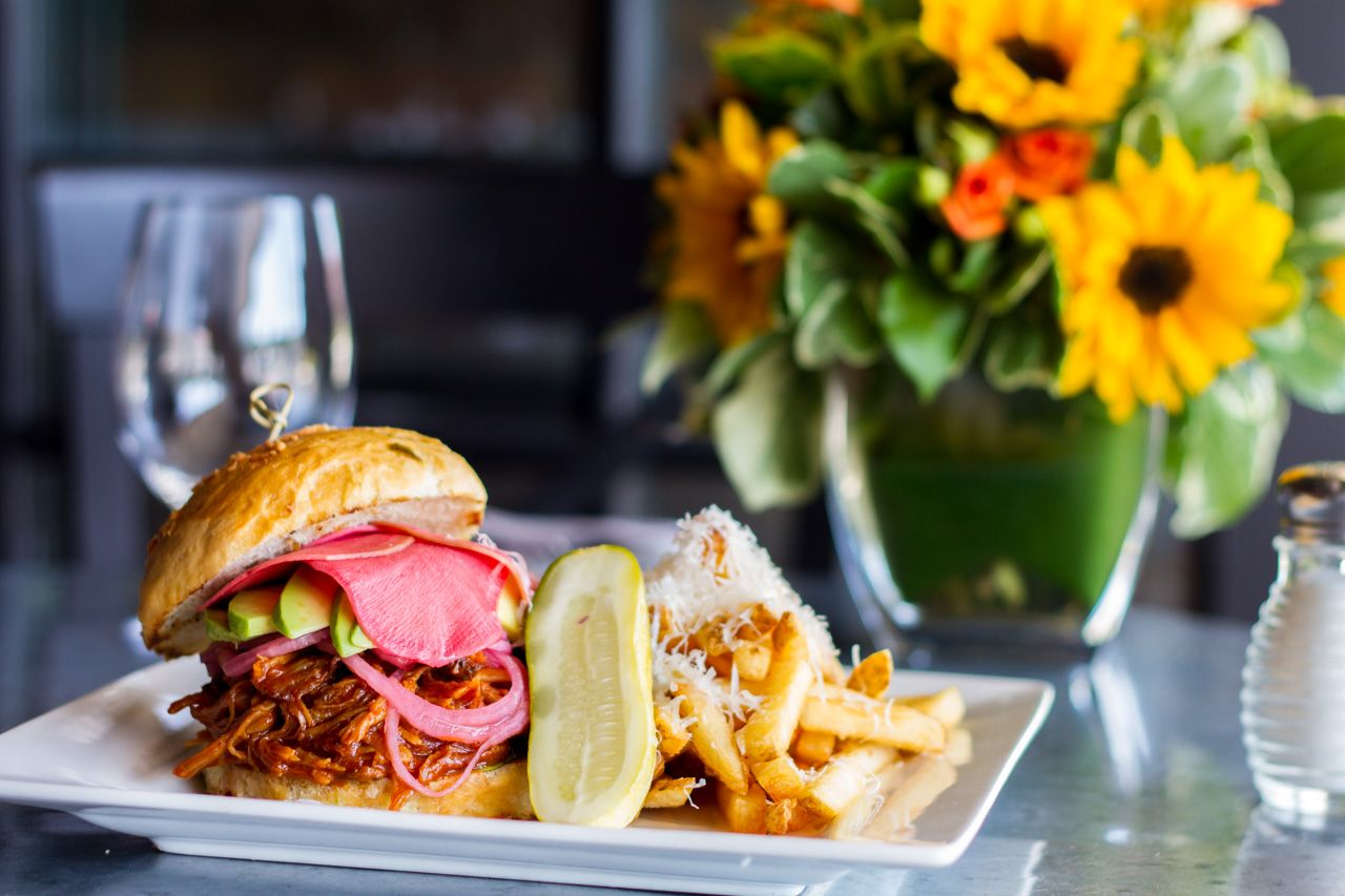 bbq pulled pork sandwich: jalapeño-parmesan roll, organic apricot bbq sauce, house pickled watermelon radish and red onions, butter lettuce, pecorino truffle fries
