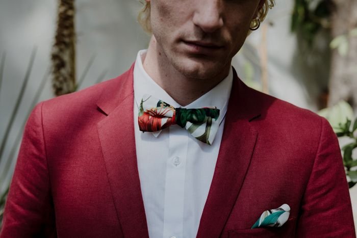 Red suit with floral bow tie and handkerchief to subtly tie in their greenhouse setting | Image by Days Made Of Love