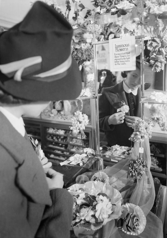 A woman pins a luminous flower to her jacket lapel in Selfridge's department store, London, 1940.