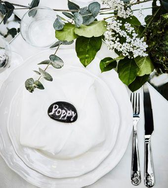 Et bryllupsbord med hvitt servise, en hvit serviett og en glitrende, malt stein brukt som bordkort