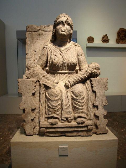 Escultura en piedra de mujer sentada, hierática, que mira de frente al espectador. Sobre su regazo, fajados y colocados uno frente al otro, dos niños de corta edad.