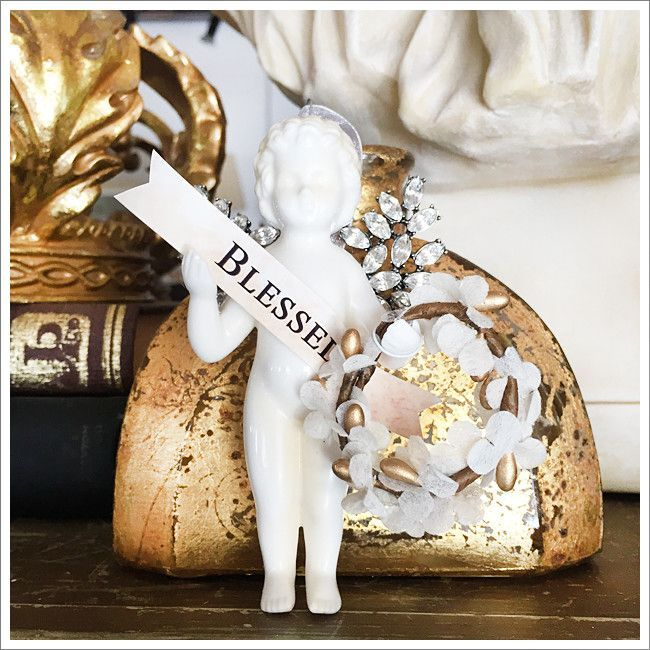 """A gorgeous glazed ceramic cherub ornament, adorned with lovely """"Blessed"""" banner and rhinestone prong-set wings. Holding a delicate, vintage-inspired wreath. Sure to become an heirloom. Approximately 5"""