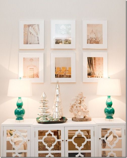 Love this pretty white console with turquoise lamps and that grouping of framed prints are really striking.  A simple grouping of mercury glass trees adds a festive touch.