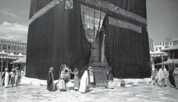 صورة عام ١٣٦٧هـ للكعبة والطائفين والحجر الأسود وبجواره أحد الحراس بزيه الرسمي @Haramain_Pic