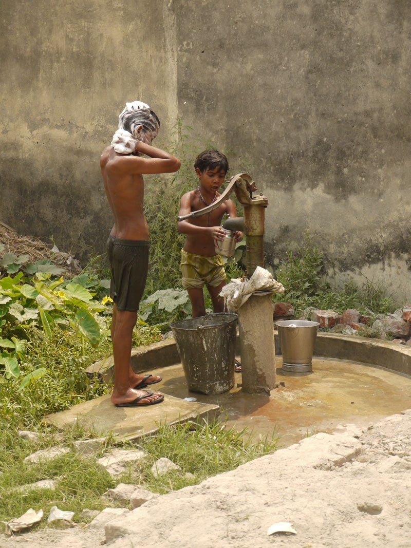 Youngsters wasing at a well in the 48degree heat in Kushinagar, India