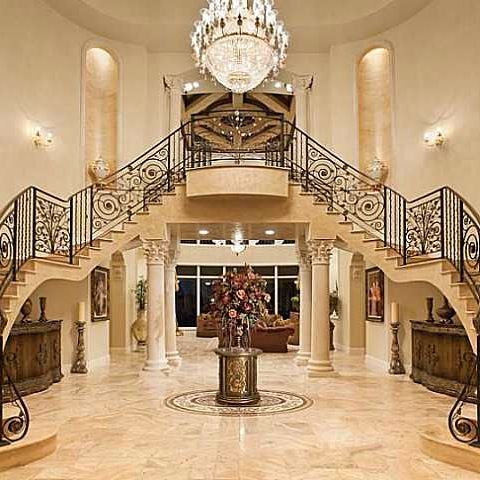 Grand foyer with custom wrought iron double staircase ...