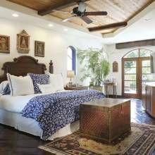 Above the bed are retablos the homeowners found in Mexico and Peru. The round nightstand has a hammered-copper base, while lamp bases are made of mercury glass. French doors lead to a private patio