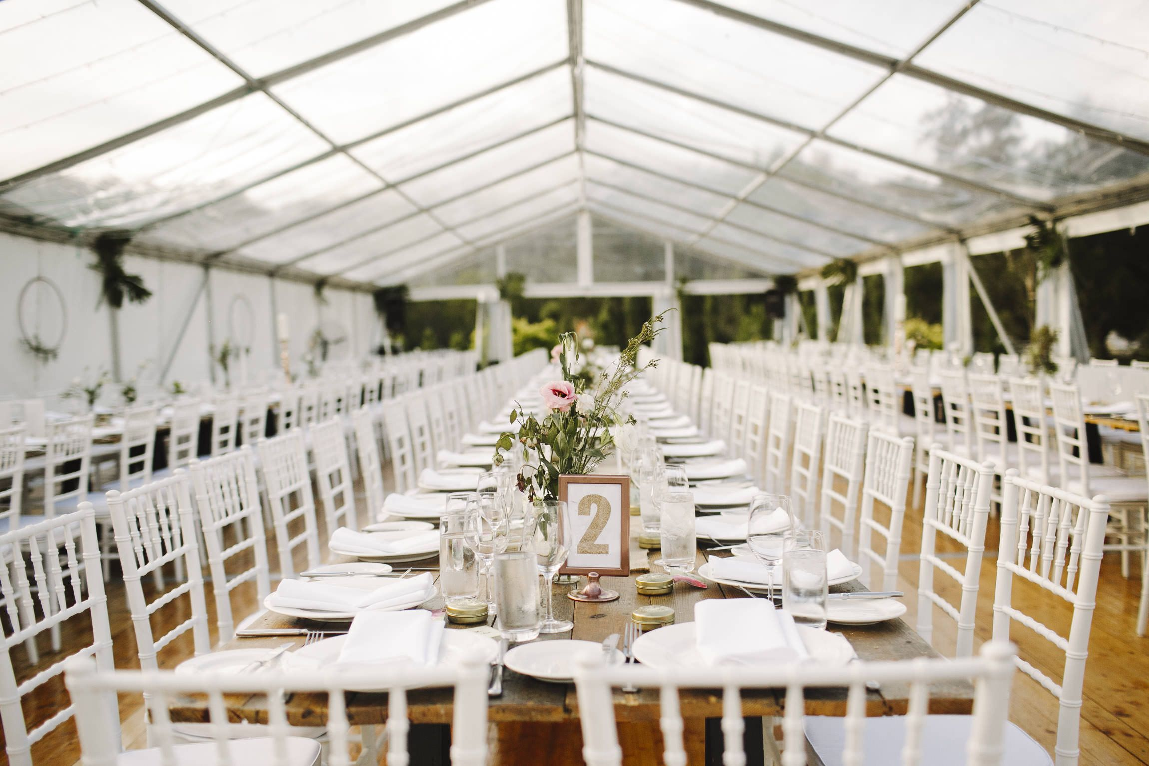 White tiffany chairs marquee structure integrated timber flooring south coast weddings south coast party hire