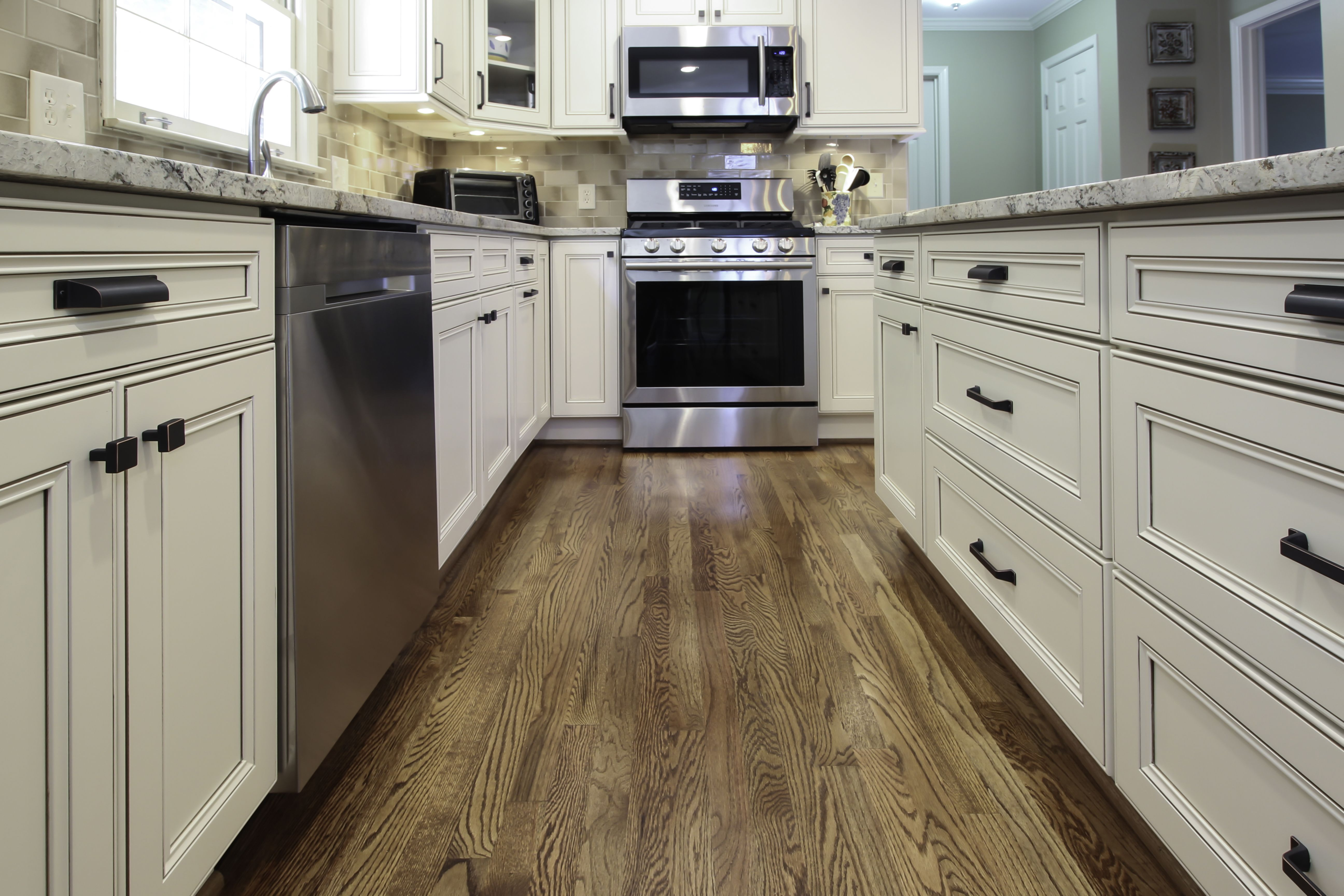Galley between perimeter and island recessed panel drawer fronts