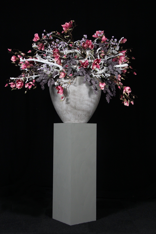 Een ronde vaas gevuld met potpourri en schelpen en een kunstbloem ...