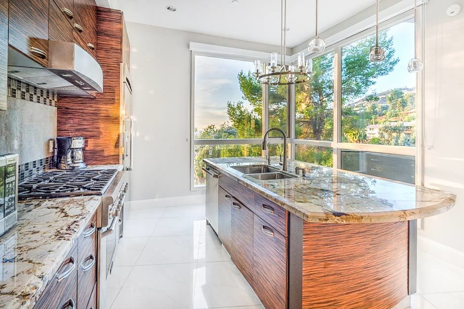 The Bohlig Residence located in Glendale, California |The outdoor deck has sleek sun loungers; the dining table has blush pink chairs and the designer kitchen is a showstopper, with views of the city to admire as you cook. #kidandcoe #bringthekids #propertyoftheday