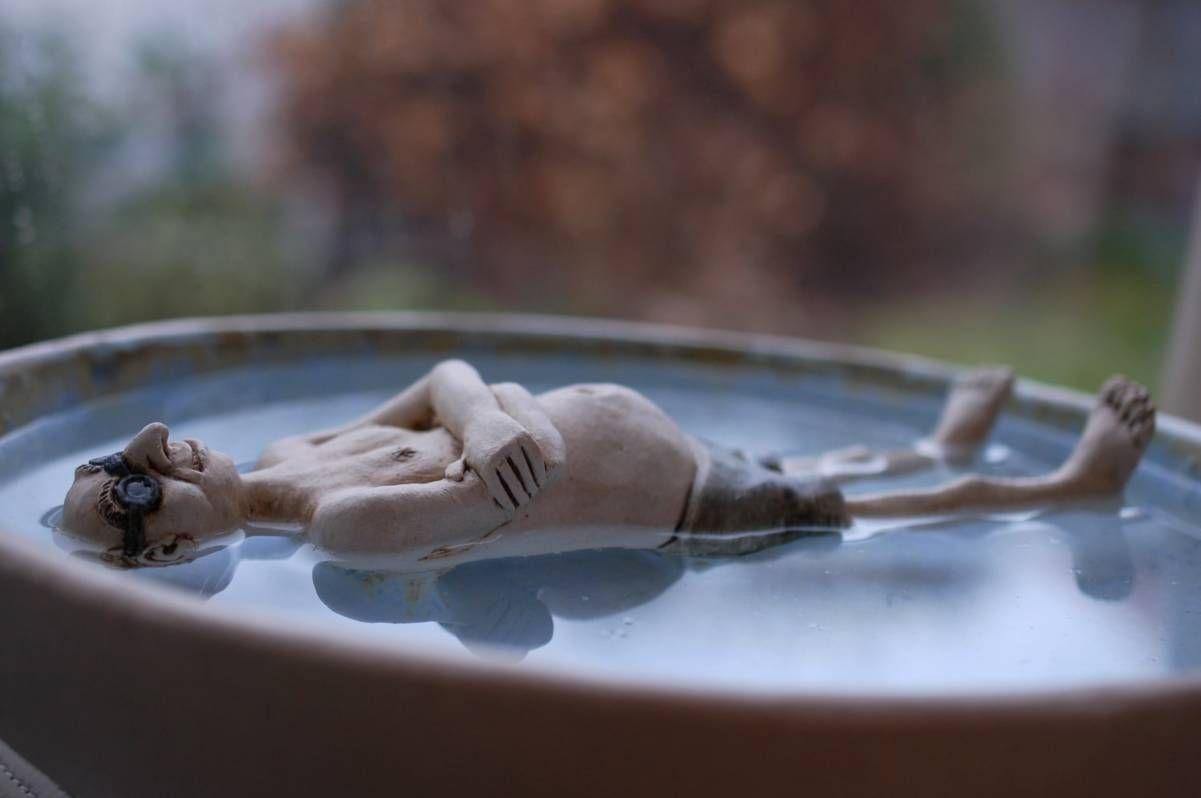 Photo of Vogelbad mit einem Mann, der auf dem Wasser schwimmt