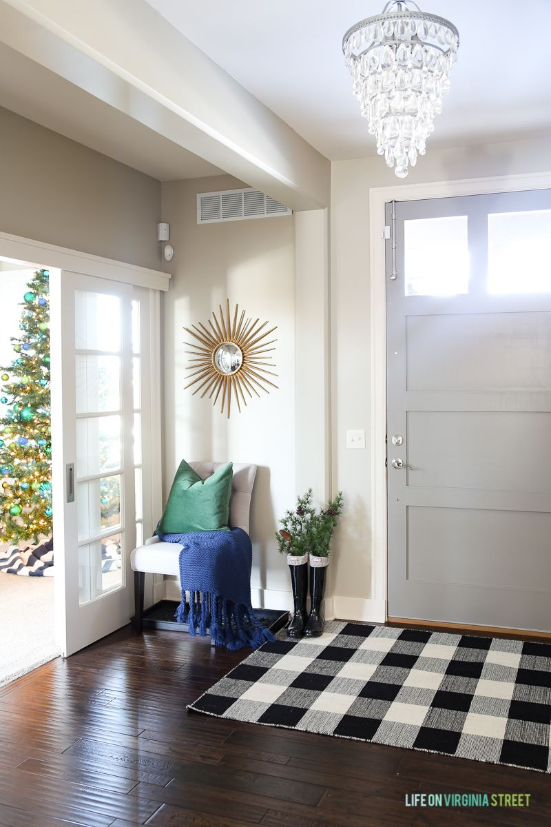 Christmas Entryway With Gray Door Buffalo Check Rug Chandelier And Blue Green Accents