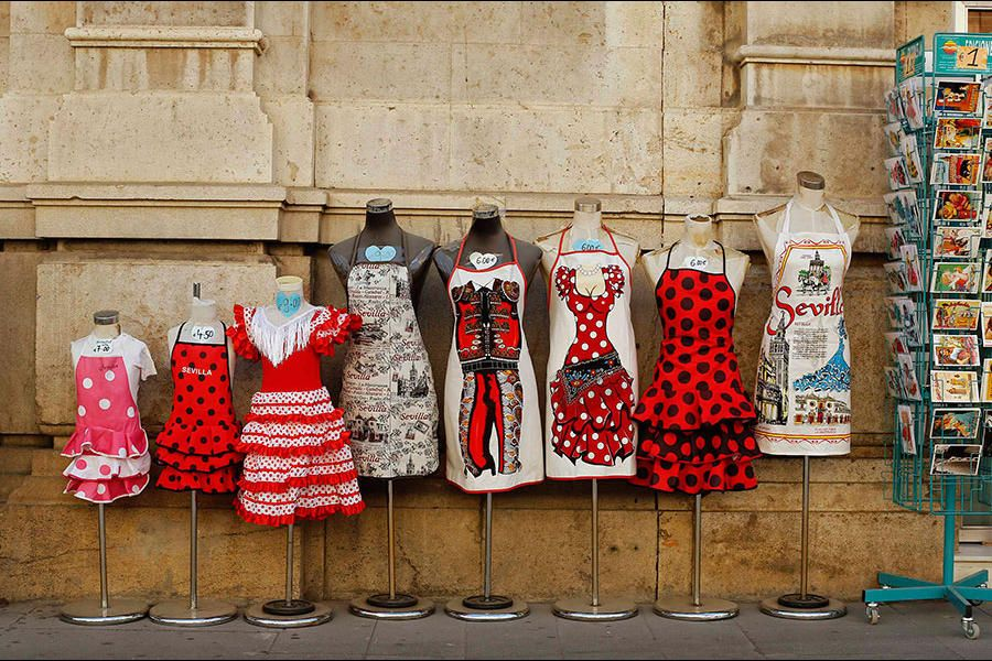Souvenir aprons and postcards are displayed for sale in the Andalusian capital of Seville, Spain. The Bank of Spain revised up its economic ...