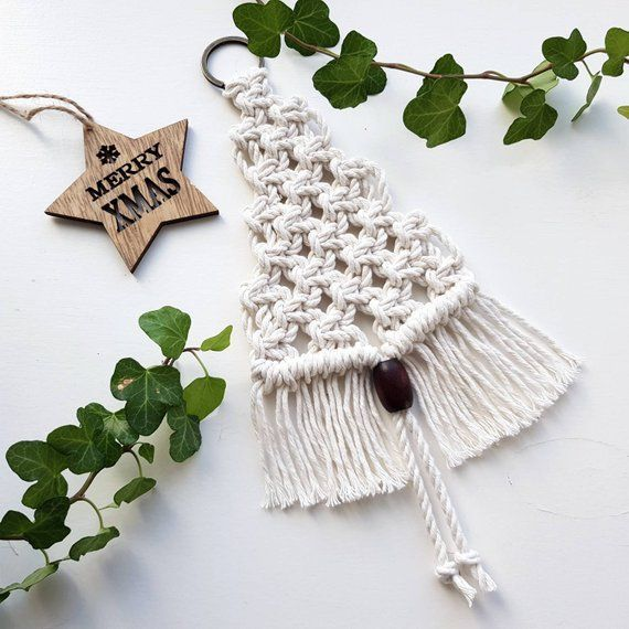 Small macrame wall pendant in the shape of a Christmas tree. The pendant is knotted of natural cotton cord of 3 mm, hangs on a bronze ring and is finished with a dark brown wooden bead. The total length of the Christmas tree is about 28 cm. At its widest point, the pendant is 11 cm - filipa mendes #macrame