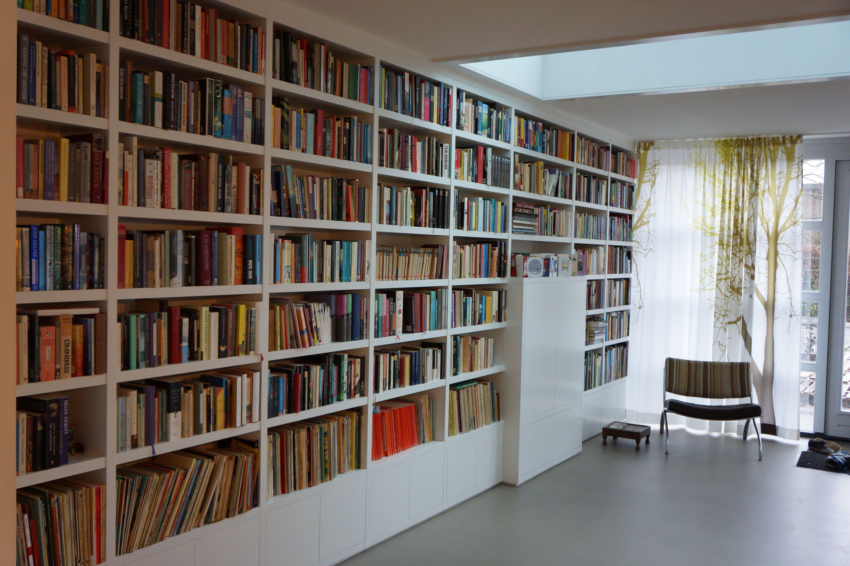 een all time favourite moderne boekenkast of eigenlijk boekenwand op maat strakke en rustige indeling van de open delen door de gelijke vakken