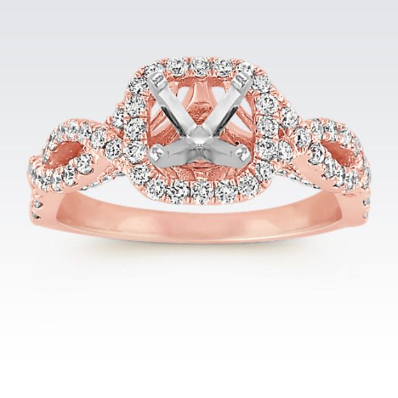 Gorgeous waves of swirls create the infinity design of this ring and lead to a lovely halo setting. This engagement ring is crafted of quality 14 karat rose gold and is accented by 94 round paveé-set diamonds, at approximately .70 carat total weight. Complete this setting with the 1.00 carat center diamond of your choice. Popular choices of center diamond shaped for this setting include princess cut, cushion cut, and round.