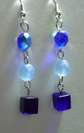 Shades of Blue. Designed by Prairie Pine Peddler can be reached for purchase at pinepeddler at gmail dot com. Bottom bead is cobalt cube, the top two beads are 6mm round faceted Czech bead. Ear wires are nickel free.