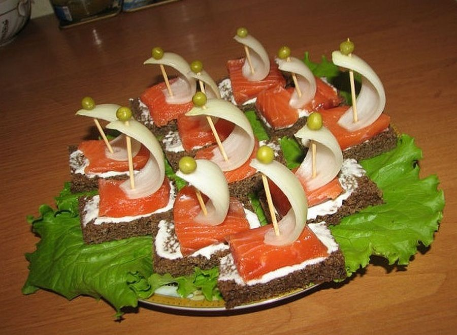 Червона риба, вершковий сир, лусочка цибулі, горошинка, скріплені шпажкою, на шматочку чорного хліба.