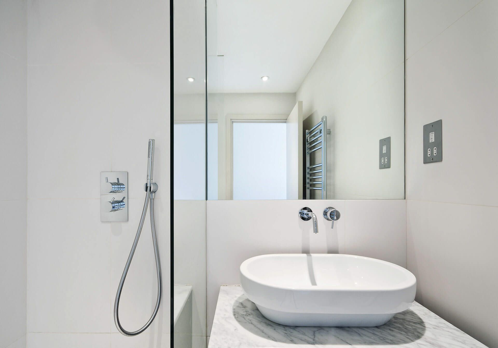 White bowl wash hand basin on counter top with wall mounted taps, flush mirror and glazed shower screen.
