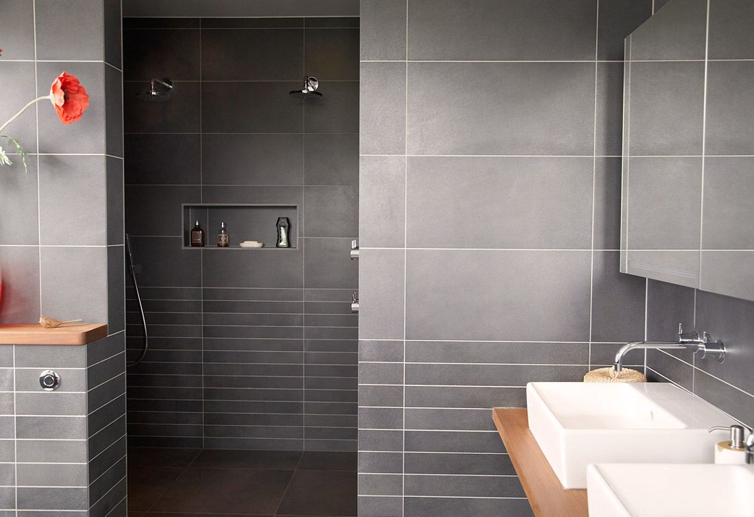 Imagem de http://chantiki.com/wp-content/uploads/2015/05/bathroom-modern-bathroom-design-with-grey-tile-wall-plus-shower-room-and-brown-bathroom-table-with-double-white-sinks-also-mirror-decorated-with-beautiful-flower-on-brown-table-combine-with-grey-tile.jpg.
