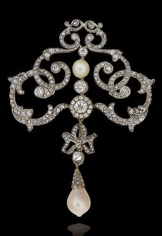 A Belle Epoque diamond and pearl corsage brooch/pendant, circa 1900. The openwork scrolling cartouche set with old brilliant and rose-cut diamonds, set to the centre with a 7.0mm pearl and a brilliant-cut diamond cluster, suspending a pearl drop with rose-cut diamond bow surmount, mounted in silver and gold, length 8.7cm. #BelleÉpoque #brooch #pendant