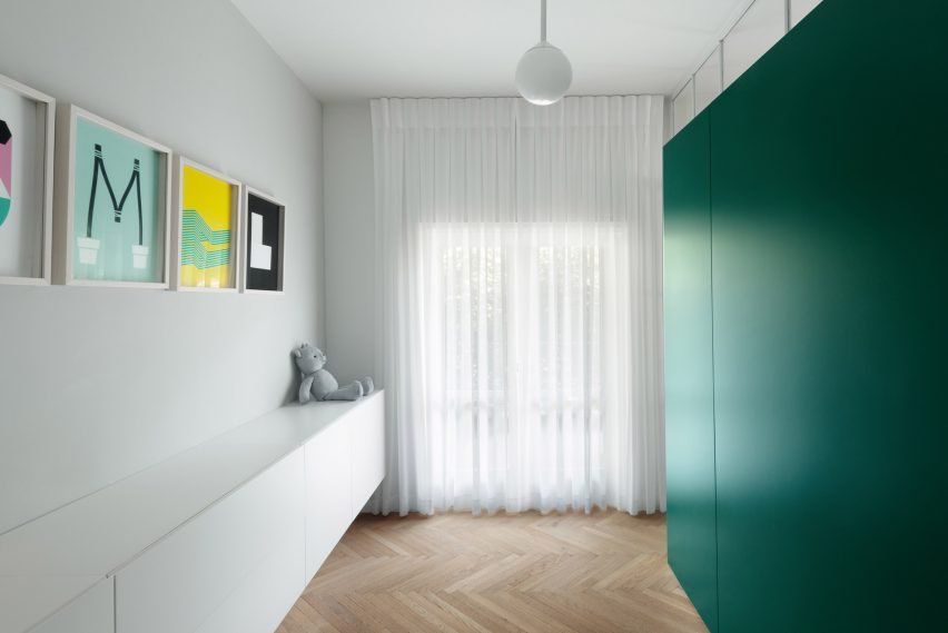 Colourful cabinetry offsets white interior of Bauhaus apartment in