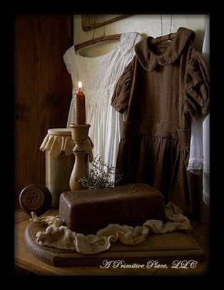 Antique Dresses, candlelight, a butter stamp, covered crock, and a pantry loaf on a breadboard.