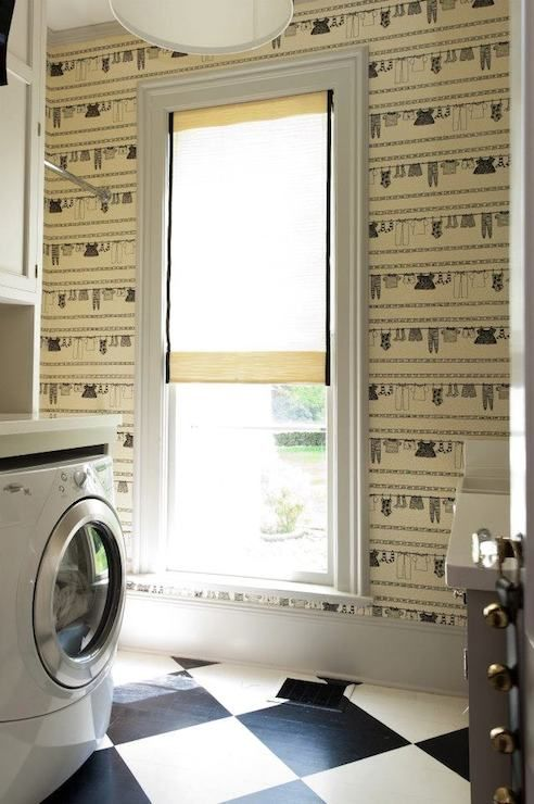 Fun laundry room features walls clad in cream and black ...