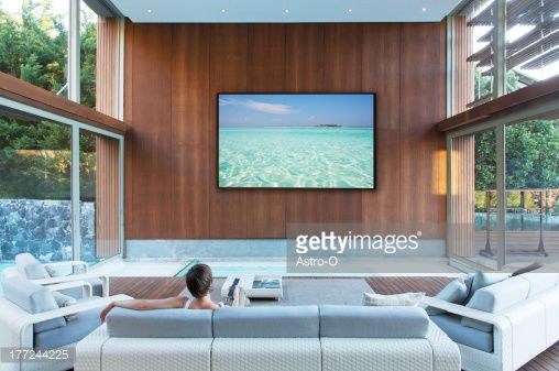 Stock Photo : Woman watching large flat screen TV in modern living room