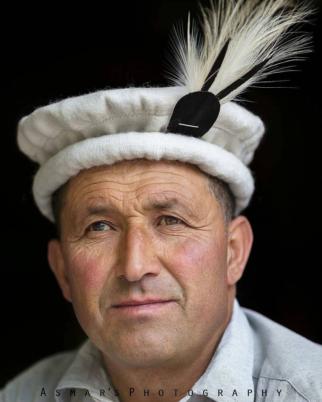 A Hunza man wearing traditional cap with feather.  38106a5712fb