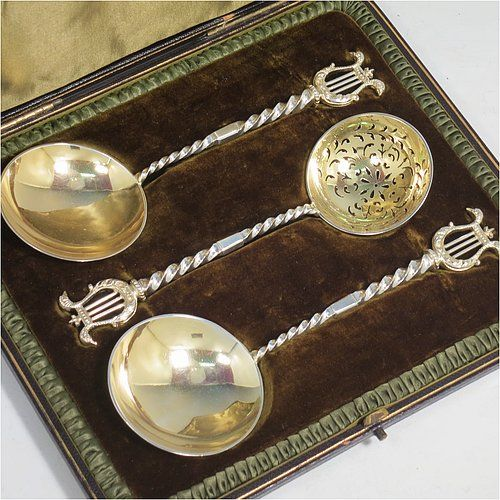 An Antique Victorian Sterling Silver and gold-gilt serving spoon set, consisting of a pair of serving spoons and a sugar sifting ladle, having cast handles with twisted stems and Lyre shaped terminals, and with gold-gilt bowls, and all sitting in an original olive green satin and velvet-lined presentation box. Made by Holland, Aldwinckle, & Slater of London in 1895. The dimensions of this fine hand-made set of antique silver serving spoons are length 17 cms (6.75 inches), and they weigh a…