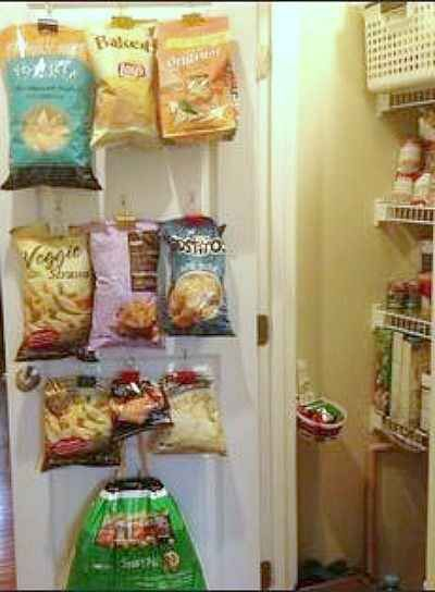 Command hooks and binder clips create an ideal bag display on the inside of a pantry door.