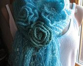 A small elegant turquoise scarf with tassels. It can decorate clothes and outerwear. There are  3 flowers included with the scarf . All flowers are removable and fixed as a brooch. Therefore, they can be separated from the scarf and put on a dress, jacket, coat or even a bag. Main cloth scarf is knitted, flowers are crocheted.   Yarn: mohair, acrylic.