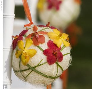 The Ceremony Decor The wedding aisle was decorated with floral pomanders accented with yellow, red, and orange Mokara orchids. The arrangements were tied to the bright white chiavari chairs with sheer orange ribbon.