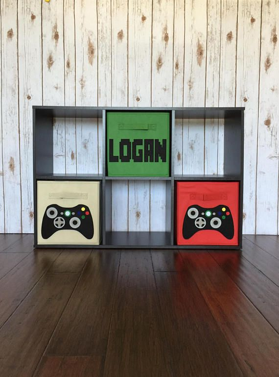Kids Video Game Storage Bin, Set of 3, Video Game Decor, Gamer Decor, Fabric Bin, Kids Bedroom Decor, Boys Room Decor, Boys Bedroom Decor is part of Boys bedroom Gamer - This kids video game storage bin set is a great addition to the video game décor of any child's bedroom or playroom! This set of three bins comes with two video game controllers (other style controller options are available) bins, and one personalized bin (font can be customized)   Please leave your bin color choices and the name in the notes to seller   This video game storage bin set is a great way to add that extra storage into your child's space  These storage cubes are an awesome way to match or set the theme of your child's room without breaking the bank  They are great for stashing toys, books or clothes    and of course video games!!!  I use quality Closetmaid brand bins   This storage bin set is the standard size of 10 5 x 10 5 x 11  This set of six should be compatible with 11  six cube organizer shelves found at most big box retailers  I'm a fan of Target's Room Essentials brand cube shelves  These designs can also be done in the larger 13  bin size   Simply message me or request a custom order  Please visit my store policies for important information about shipping and returns  Do not hesitate to contact me with any questions and thanks for stopping by!