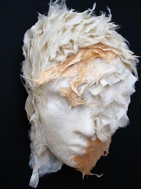 """Diane Hebert uses handmade paper as a medium for sculpture in her art exhibit, """"Masks"""".  She uses Kozo bark pulp and fiber embedded with plant materials in her sculptures, """"leading the Kozo pulp and fiber in a dance with the plants and other natural materials"""