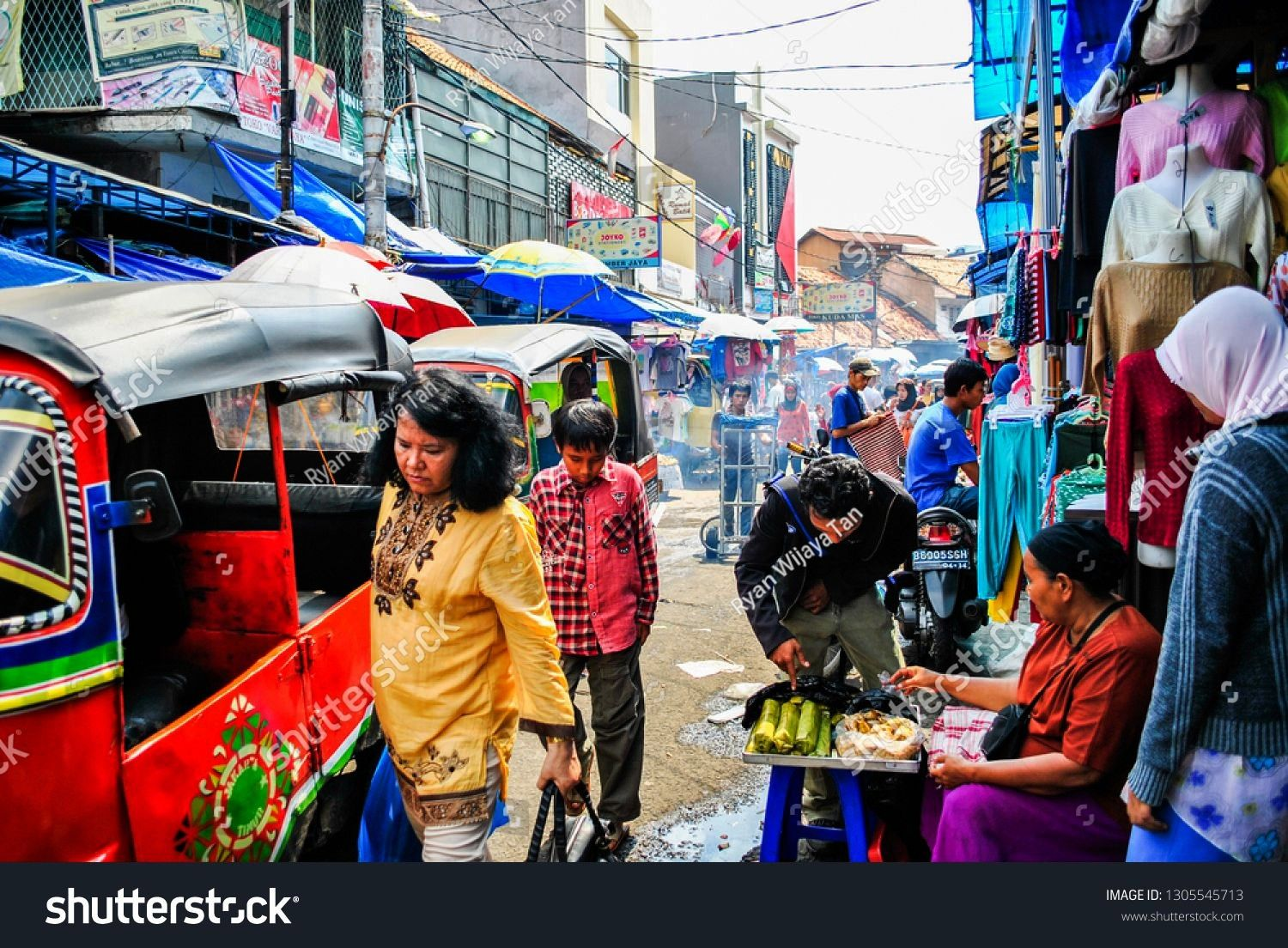 Indonesia  December 19 2009 Crowded street market in Jakarta with public transport bajaj people old buildings and street vendors street food and fruits seller Jakarta Ind...