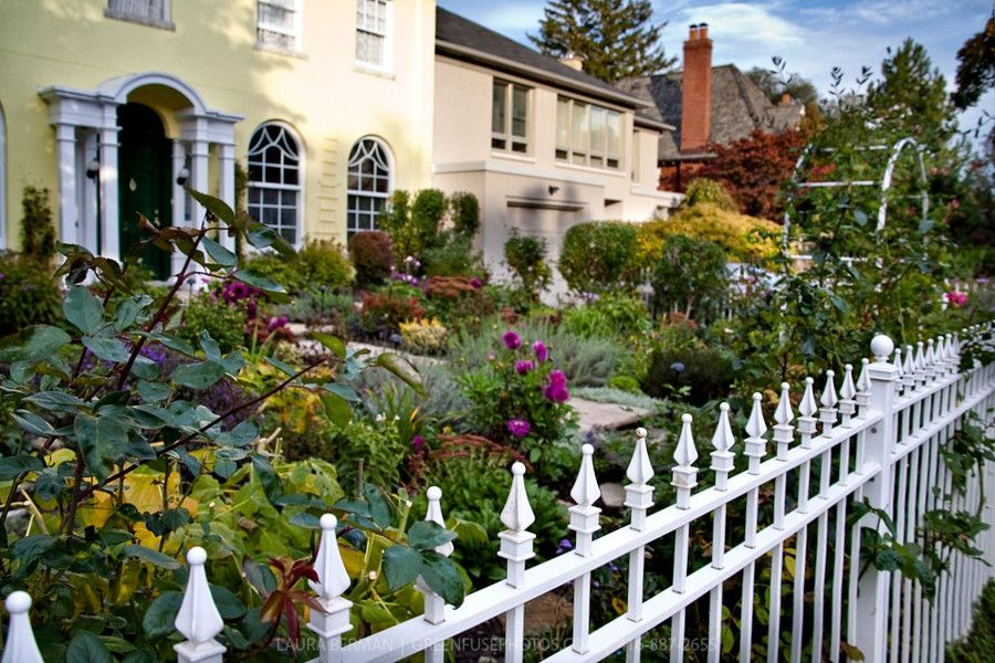 A White Wrought Iron Picket Fence Encloses An Entry Garden