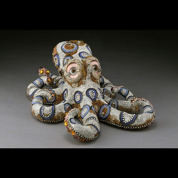 This one of a kind mosaic sculpture captures the playful movement of the blue-ringed octopus. Otto is covered in glass beads, vintage glass jewelry components, and has antique hand blown glass eyes. He can be wall hung or placed on a flat surface. Otto has a surprise on his underside. This piece was a true labor of love.