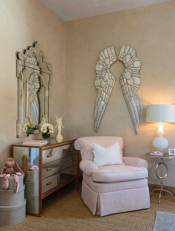 Sat catty corner on a bound sisal rug under RH Baby & Child Pewter Angel Wings, an adorable pink skirted glider is positioned between a mirrored dresserand a round silver accent table illuminated by a white double gourd lamp.