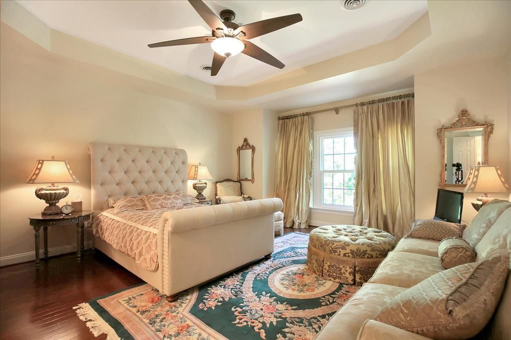 A tray ceiling with ceiling fan chandelier light caps the elegant ...